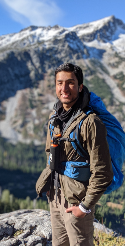 Traveler with backpack smiling in front of mountains