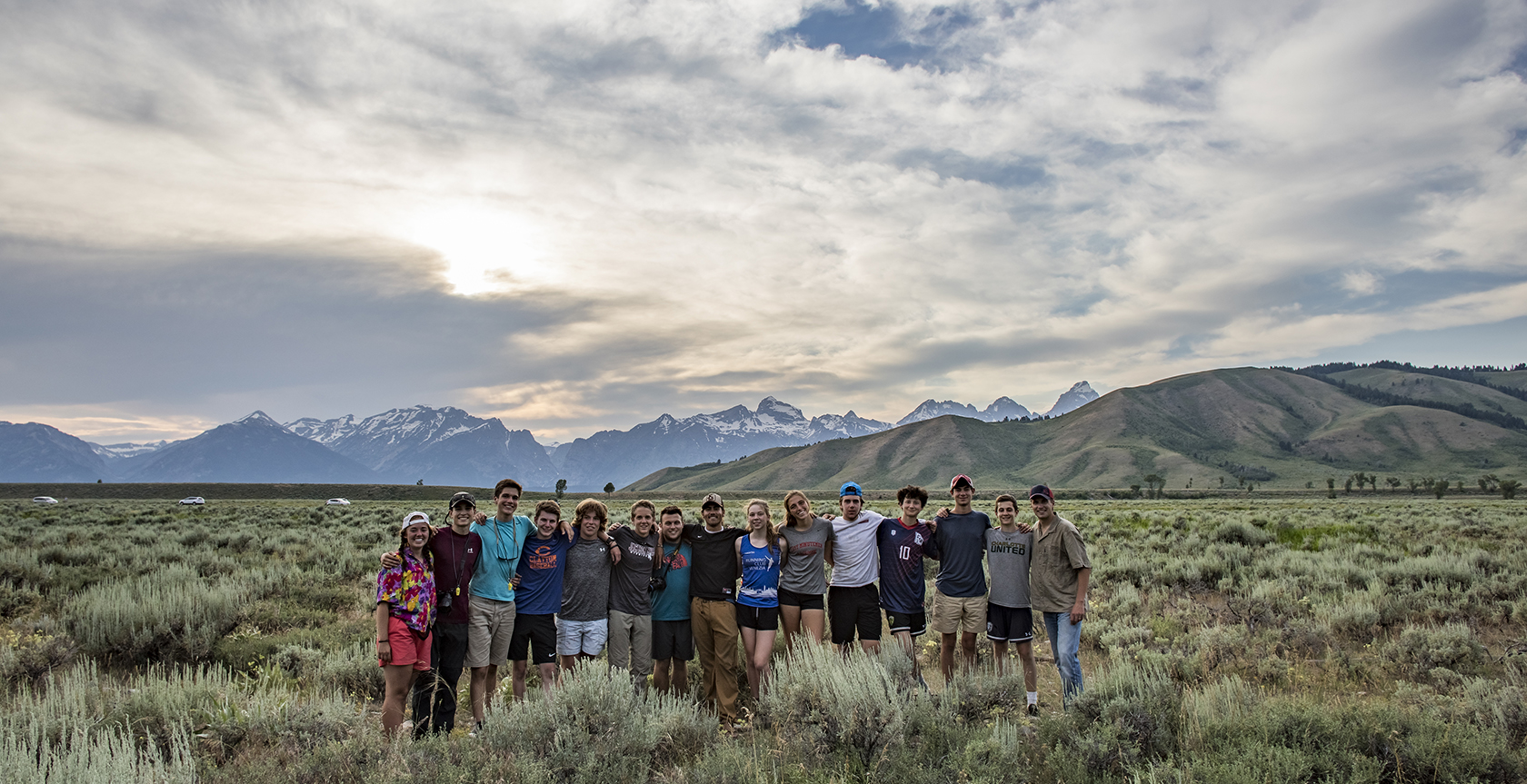 group of kids standing arm in arm outside sunset and mountains