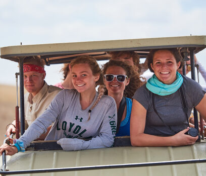 Travelers in a golf cart smiling