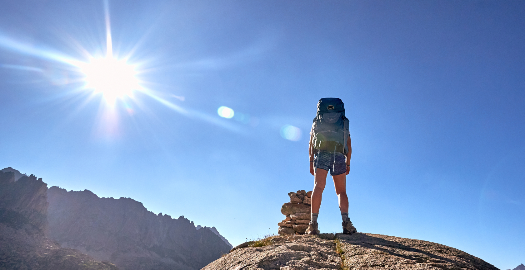 Traveler standing on top of a rock with the sun shining on them